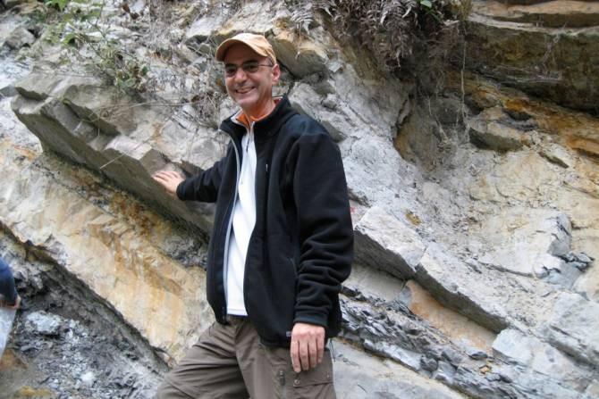Daniel Rothman, profesor de geofísica en el MIT, junto a una parte de la Formación Xiakou en China. Su mano derecha descansa sobre la capa que marca el momento de la extinción masiva de finales del Pérmico. Muestras de esta formación proporcionaron evidencias de grandes cantidades de níquel que fueron arrojadas al medio ambiente por la actividad volcánica en aquel entonces, hace 252 millones de años. (Foto: Cortesía de Daniel Rothman)